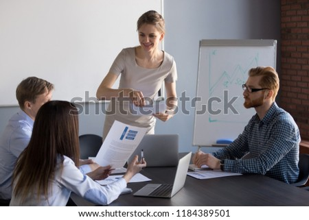 Smiling female ceo leader giving team members papers financial report with good work results, happy businesswoman presenting partners documents with new project business plan at group meeting