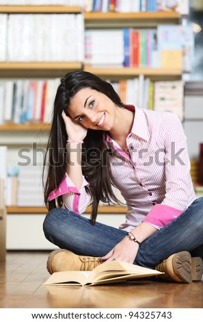 smiling female college student sitting on floor in library, reading book - stock photo