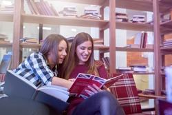 Smiling female college students studying in library