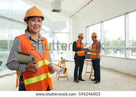 Smiling female construction site engineer with digital tablet