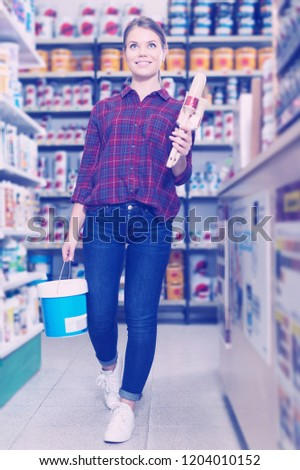 smiling female designer is holding paint and brushes for redecorate room in the store.