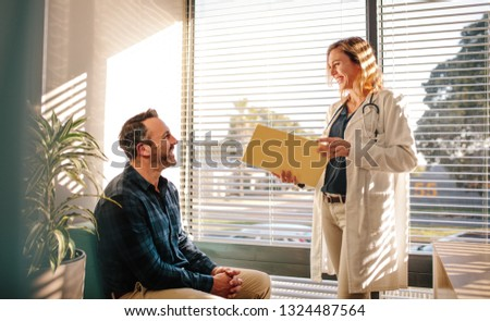 Smiling female doctor holding a medical report file and talking with male patient sitting on sofa at hospital reception. Doctor sharing good medical test results with the patient.