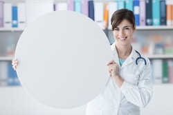 Smiling female doctor holding a round white sign, blank copy space, healthcare concept