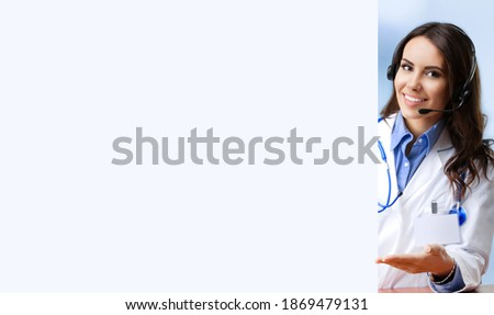 Smiling female doctor in phone headset, showing empty sign board with copy space blank area for text. Medical call center, clinic consulting, consultation, help answering. Skype, zoom online helping.