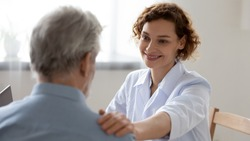 Smiling female doctor reassuring supporting senior adult patient in hospital. Kind caring young woman nurse or caregiver helping older retired man talking, giving comfort, expressing care concept.