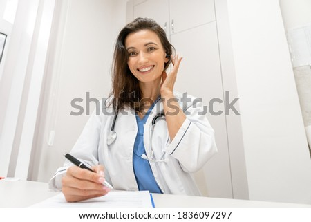 Smiling female doctor wear headset make online telemedicine video call consult patient and writing notes. Woman therapist talking to camera in remote videoconference chat. Webcam view, face headshot
