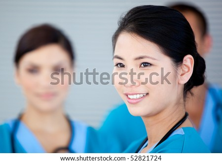 Smiling female doctor with her teamates in the hospital - stock photo