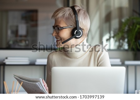 Smiling female employee in headset make notes talk on video call with colleague or client working on laptop, woman worker busy brainstorming have online briefing web conference with coworker at home