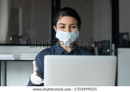 Smiling female employee in protective face mask and rubber gloves work on laptop in office, positive woman worker consult client online on quarantine against COVID-19, corona, healthcare concept