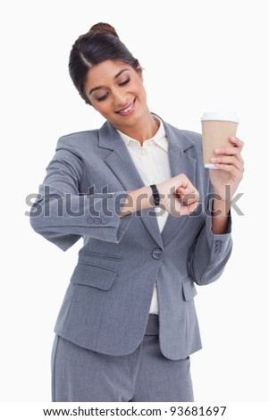 Smiling female entrepreneur with paper cup looking at her watch against a white background