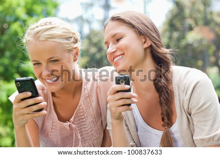 Smiling female friends with cellphones