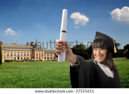 Smiling female graduate with diploma and a university on the background