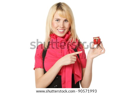 Smiling female holding a small gift box and pointing at it, isolated on white background