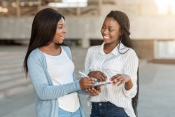 Smiling female interviewer conducting survey with young african american woman on street