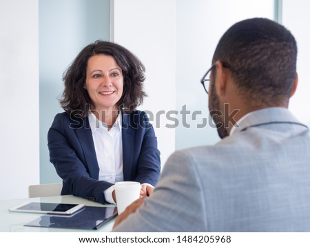Smiling female job candidate talking to employer during interview. Business man and woman sitting at meeting table and talking. Career concept