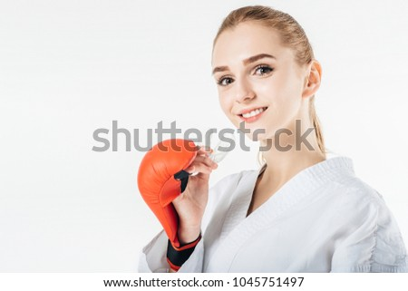 smiling female karate fighter holding mouthguard isolated on white #1045751497