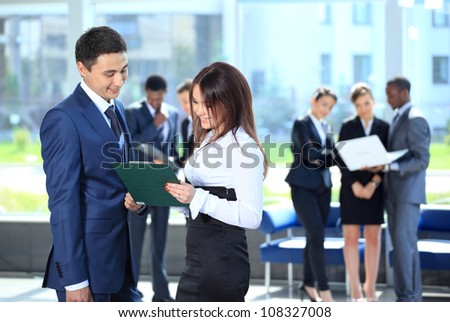Smiling female leader discussing business plan with confident colleagues