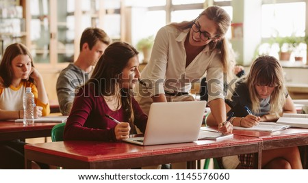 Smiling female lecturer helping student during her class. Student in a lecture with helpful teacher. #1145576060