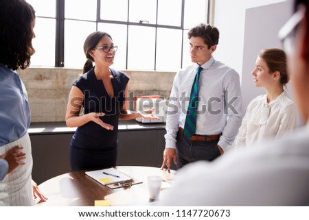 Smiling female manager in glasses addressing team in meeting #1147720673