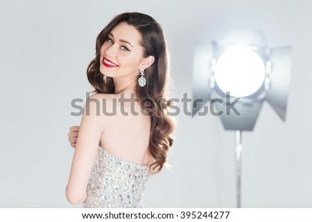 Smiling female model posing in fashion dress