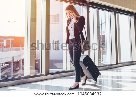 Smiling female passenger proceeding to exit gate pulling suitcase through airport concourse while talking on the phone