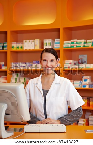 Smiling female pharmacist serving at counter in drugstore - stock photo