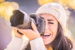 Smiling female photographer in a winter cap takes picture outdoors.