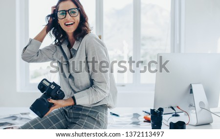 Smiling female photographer with a professional camera sitting on her desk. Woman with dslr camera in office looking away and smiling.
