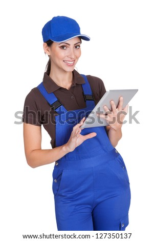 Smiling Female Plumber Working On Digital Tablet. Isolated On White