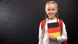 Smiling female pupil holding German language textbook, blackboard background