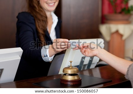 smiling female receptionist passing card to guest #150086057