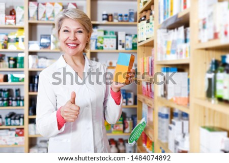 Smiling female seller offering products of skin care in specialized shop