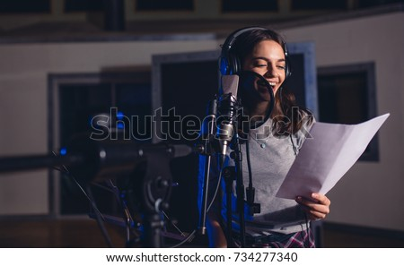 Shutterstock Smiling female singer with microphone and reading lyrics. Woman recording a song in music studio. Female playback singer recording her new album.