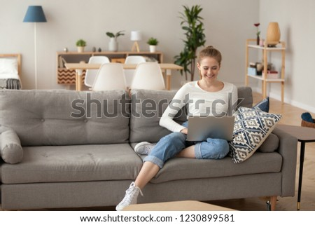 Smiling female sit on cozy couch at home with laptop on knees browsing internet, happy girl spend weekend in apartment relaxing on couch watching film on computer, woman shopping online