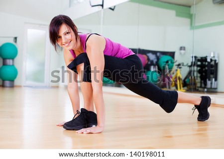 Smiling female stretching out her legs and body
