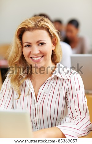 Smiling female student at laptop in university class