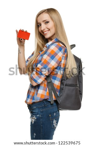 Smiling female student holding empty credit card, over white background