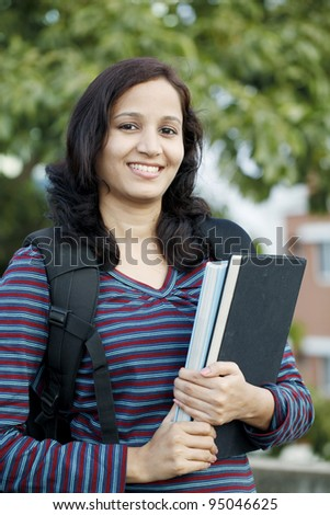 Smiling female student holding text books