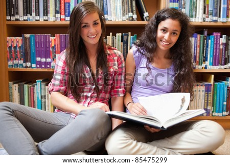 Smiling female students with a book in a library