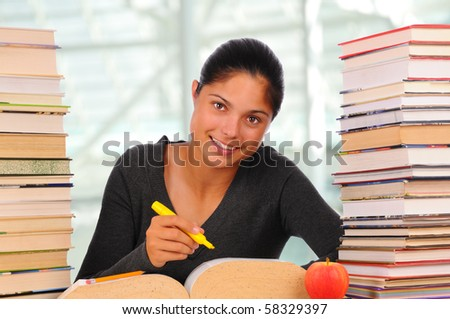 ... teenage student with long brown hair seated at desk between stacks
