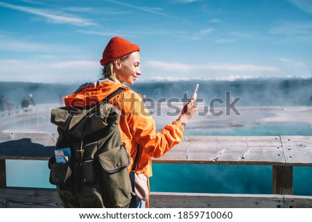 Smiling female tourist with big backpack standing near hot spring in Yellowstone National Park and doing video call on mobile phone
