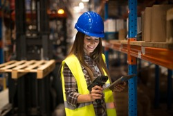 Smiling female worker holding tablet and bar code scanner checking inventory in distribution warehouse. Forklift in background.