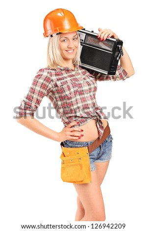 Smiling female worker with helmet listening to radio isolated on white background
