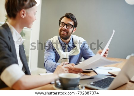 Smiling financier with papers having discussion with his associate at meeting #792887374