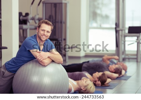 Smiling Fit Young Man Leaning on Gray Large Exercise Ball with Women at the Back Exercising. Captured Inside the Fitness Gym.