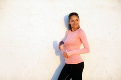 Smiling fit young woman standing on white concrete wall background with bottle of water, wearing black sport tights and pink long sleeve shirt