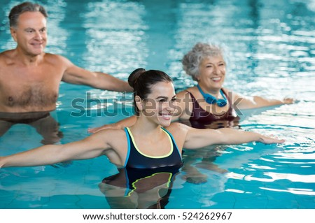 Smiling fitness class doing aqua aerobics in swimming pool. Smiling young woman with senior couple stretching arms in swimming pool. Fit mature man and old woman exercising in swimming pool.
