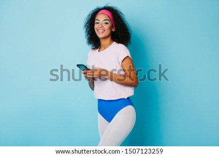 Smiling fitness girl holding smartphone. African young woman in aerobics attire posing with digital device. #1507123259
