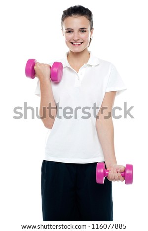 Smiling fitness teenage girl lifting weights. Exercising with pink dumbbells