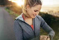 Smiling fitness woman setting a timer in her wrist watch standing outdoors. Female runner checking time in her watch during her morning run.